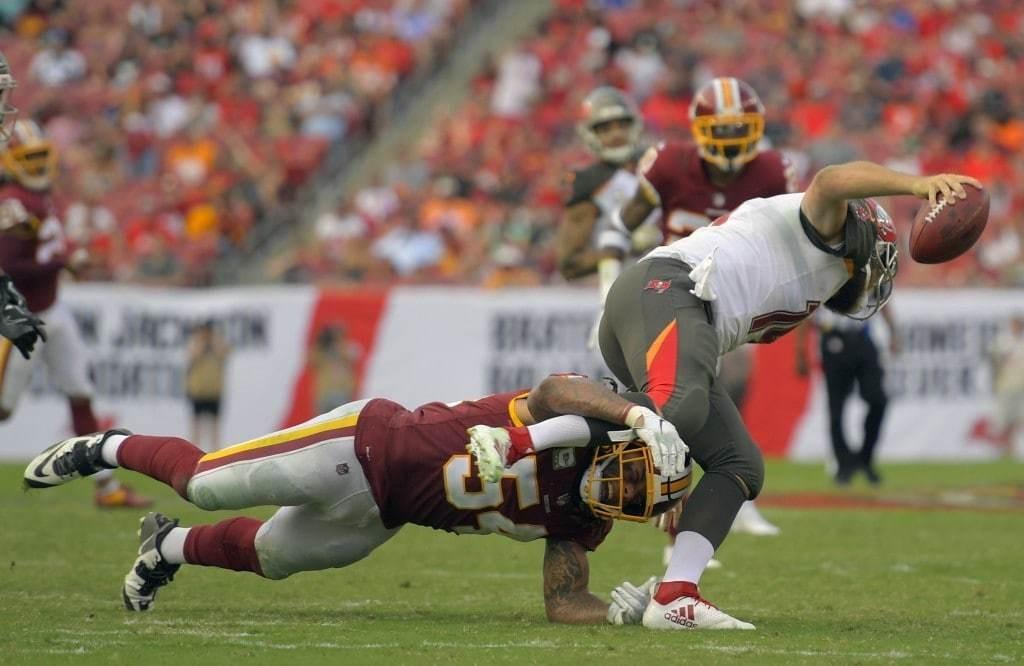 Washington Redskins inside linebacker Mason Foster, left, takes down Tampa Bay quarterback Ryan Fitzpatrick on a 4th quarter scramble. (John McDonnell/The Washington Post)