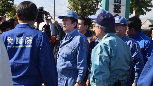 Japan PM visits typhoon-hit areas as royals signal parade delay
