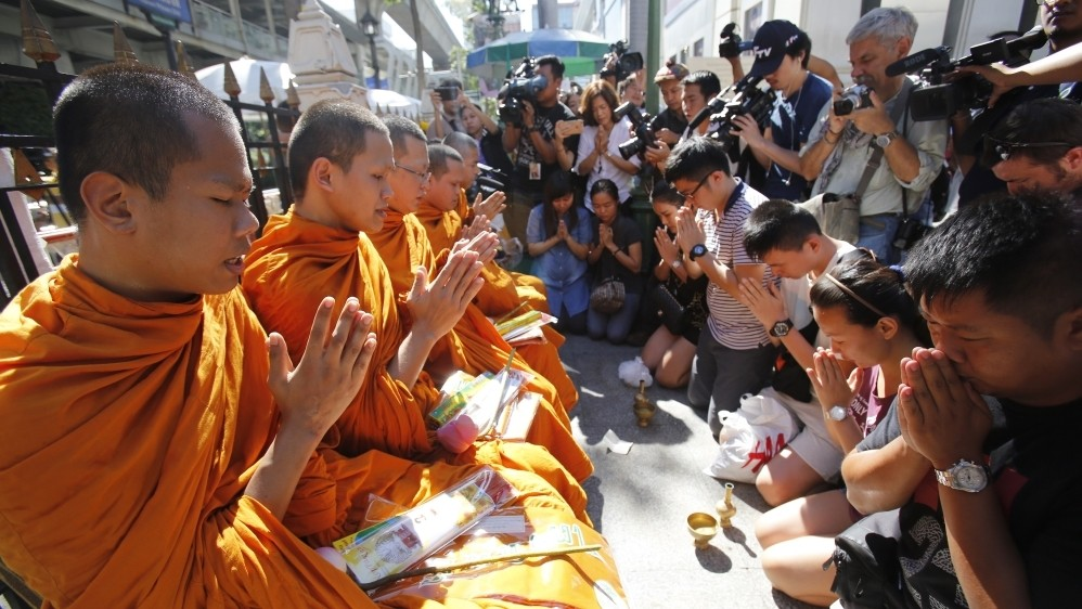 Shrine reopens in Bangkok as police hunt suspect
