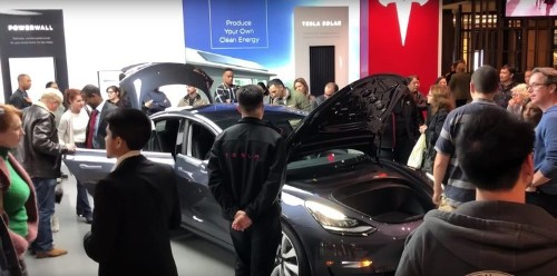 Hundreds of Tesla fans are lining up outside of showrooms to check out the Model 3