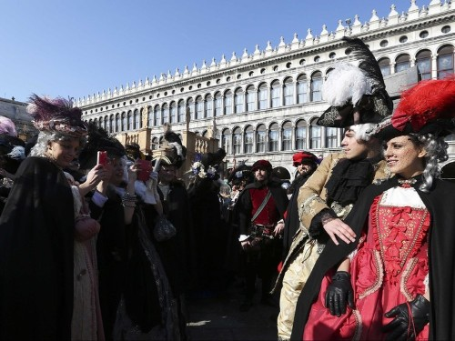 It's Carnival in Venice, and the city is completely flooded — see how revelers are dealing with all the water