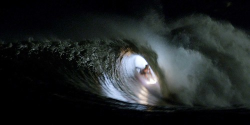 Stunning video shows people surfing at night with LED surfboards and wetsuits