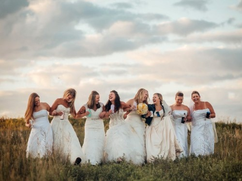 Woman takes photos with friends in old wedding dresses drinking beer