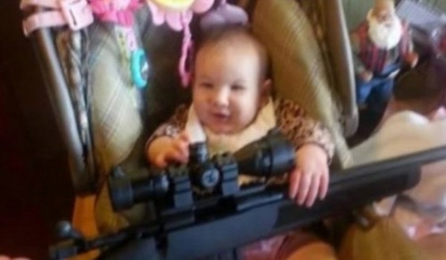 Here's The Controversial Photo Of A Smiling Baby Holding A Bolt-Action Rifle