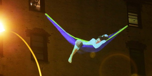 A company is projecting images of people napping on the sides of buildings in NYC