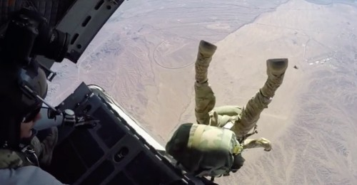 A soldier in full combat gear keeps his cool as he dangles from a military transport aircraft after a botched parachute jump