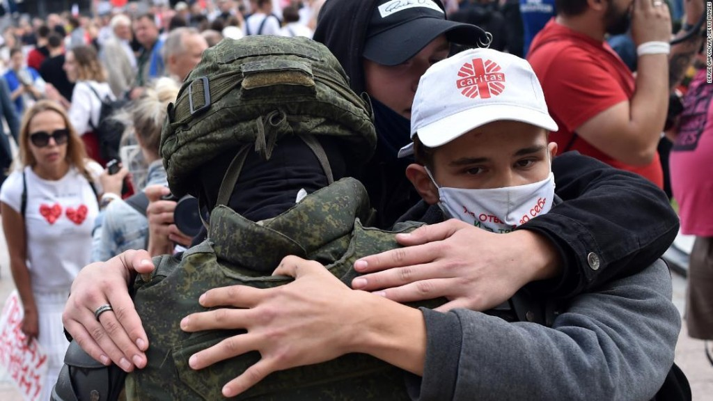 Belarus riot police drop shields and are embraced by anti-government protesters