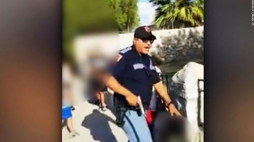 Officer points gun at a group of children