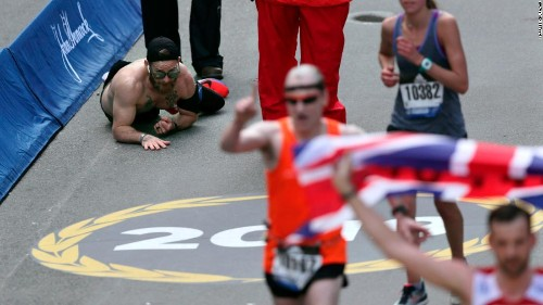 Marine running in honor of his fallen comrades crawls to the finish line of the Boston Marathon