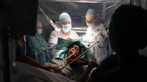 Une violoniste joue pendant son opération