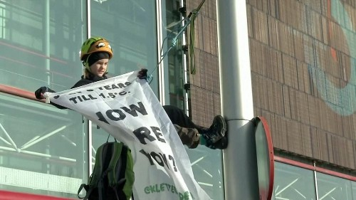 Eight-year-old scales street light in Madrid to demand climate action