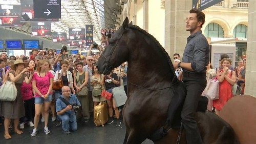 Performers on horseback surprise passengers at Paris train station