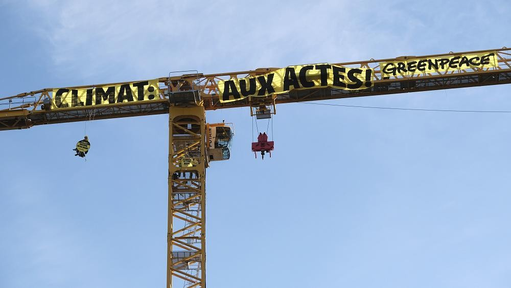 Greenpeace activists scale a crane at Notre Dame cathedral in climate protest