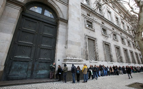 Argentines wait at banks to withdraw cash as currency controls kick in