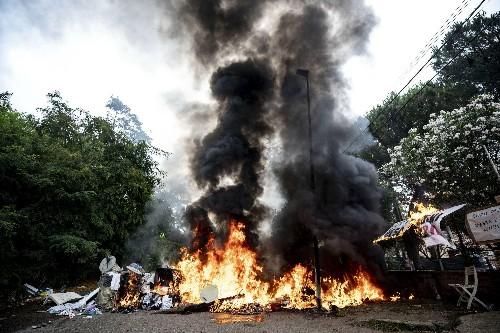 Italian police clear migrant squatters amid burning debris