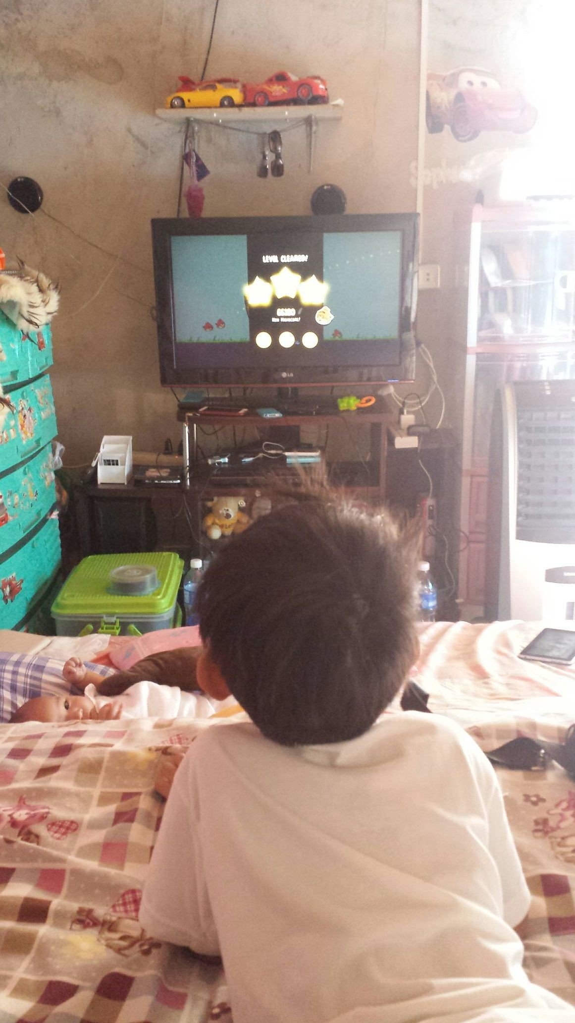 Xian playing angry bird on the big screen while xander watch
