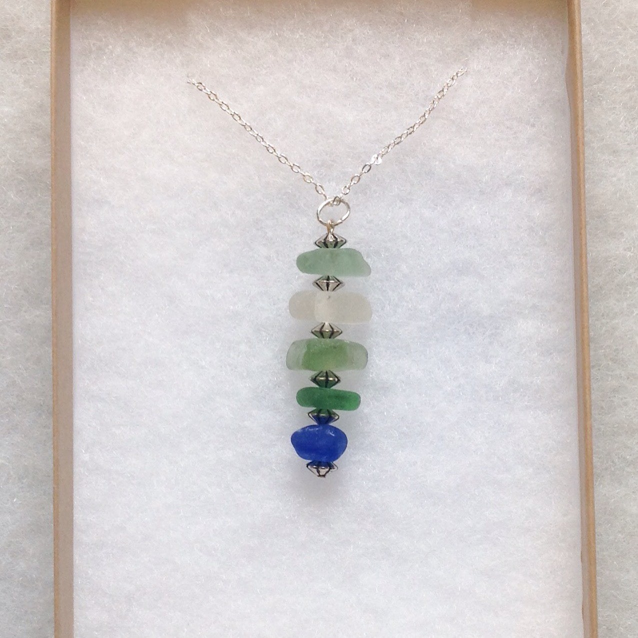 Pendant made from five translucent sea glass gems in subtle greens, cream and a fabulous rare, cobalt blue, collected from the tideline in Whitby and Boggle Hole in North Yorkshire. Beautifully smoothed by sand and sea...