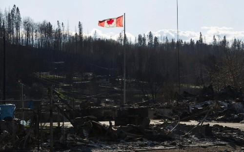 Hundreds of workers flee Canadian oil camps as wildfire continues to burn