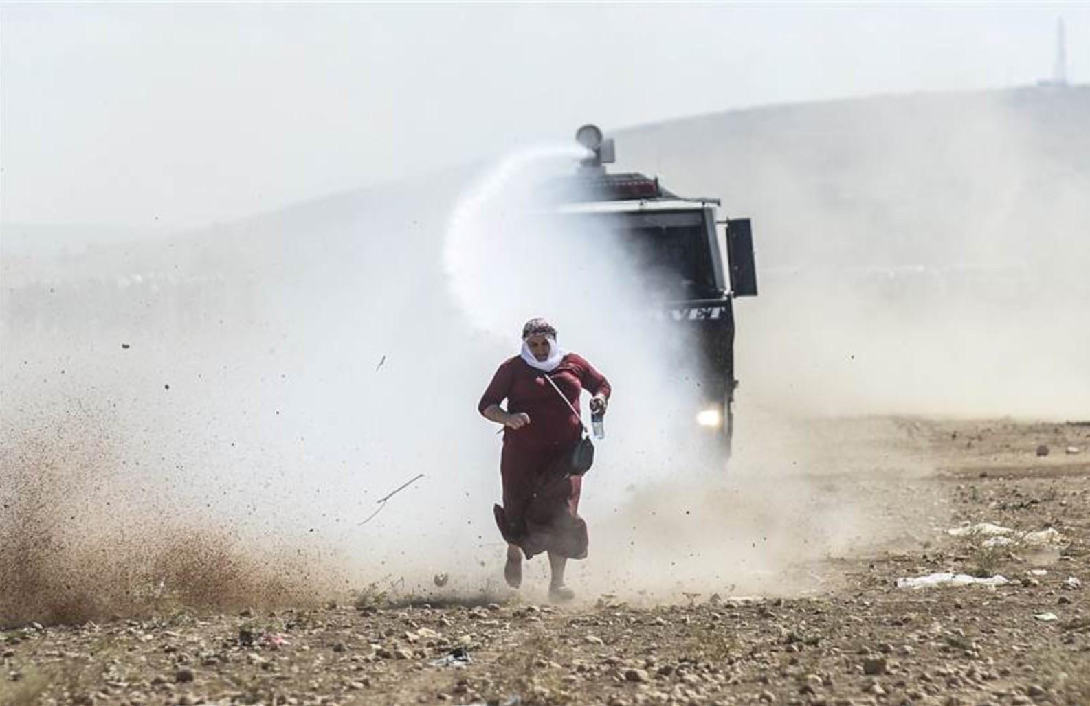 A Kurdish woman runs away from a water cannon near the Syrian border.