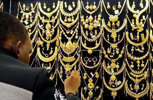Gold ticks up on Iran tensions; firmer dollar limits upside