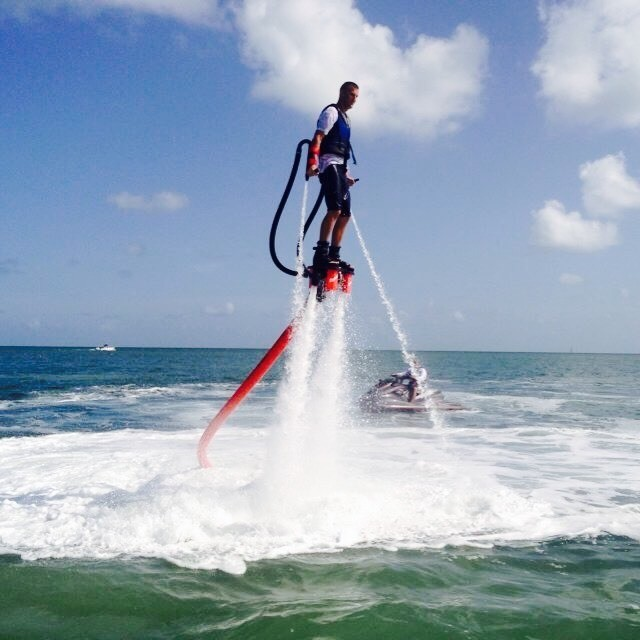 I am flyboard. A Flyboard is a type of water jetpack attached to a personal water craft (PWC) which supplies propulsion to drive the Flyboard through air and water to perform a sport known as flyboarding.A Flyboard rider stands on a board connected by a long hose to a watercraft. Water is forced under pressure to a pair of boots with jet nozzles underneath which provide thrust for the rider to fly up to 15 m (49 ft) in the air or to dive headlong through the water down to 2.5 m (8 ft).