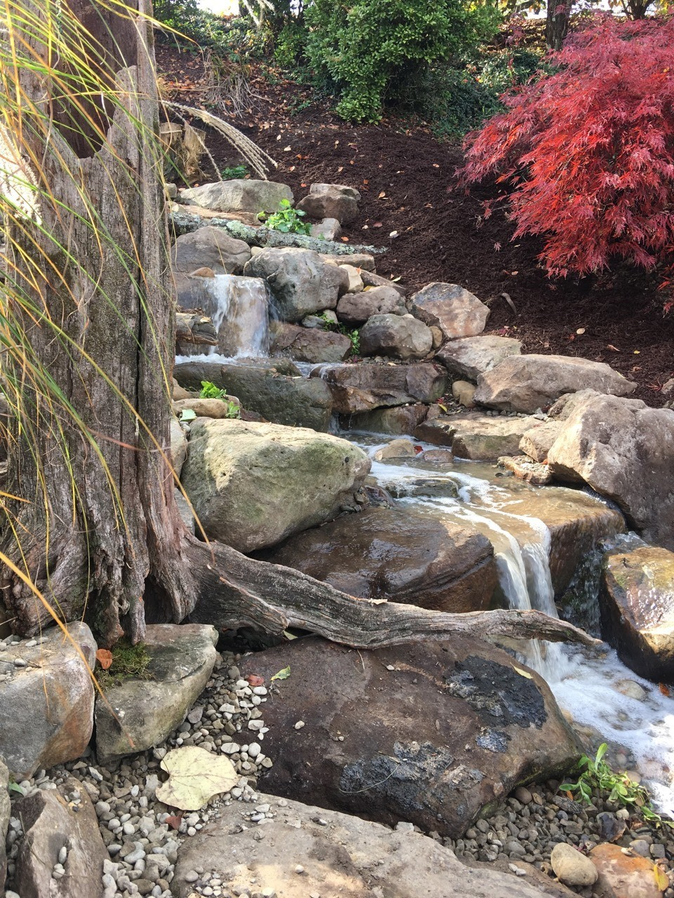 Carefully placed wood accents are prevalent in our naturalistic designs. This pondless waterfall was constructed by Aquatic Edge in the Plum area of Pittsburgh PA
