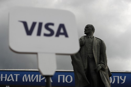 Lenin statue at final sandwiched by ads for Budweiser, Visa