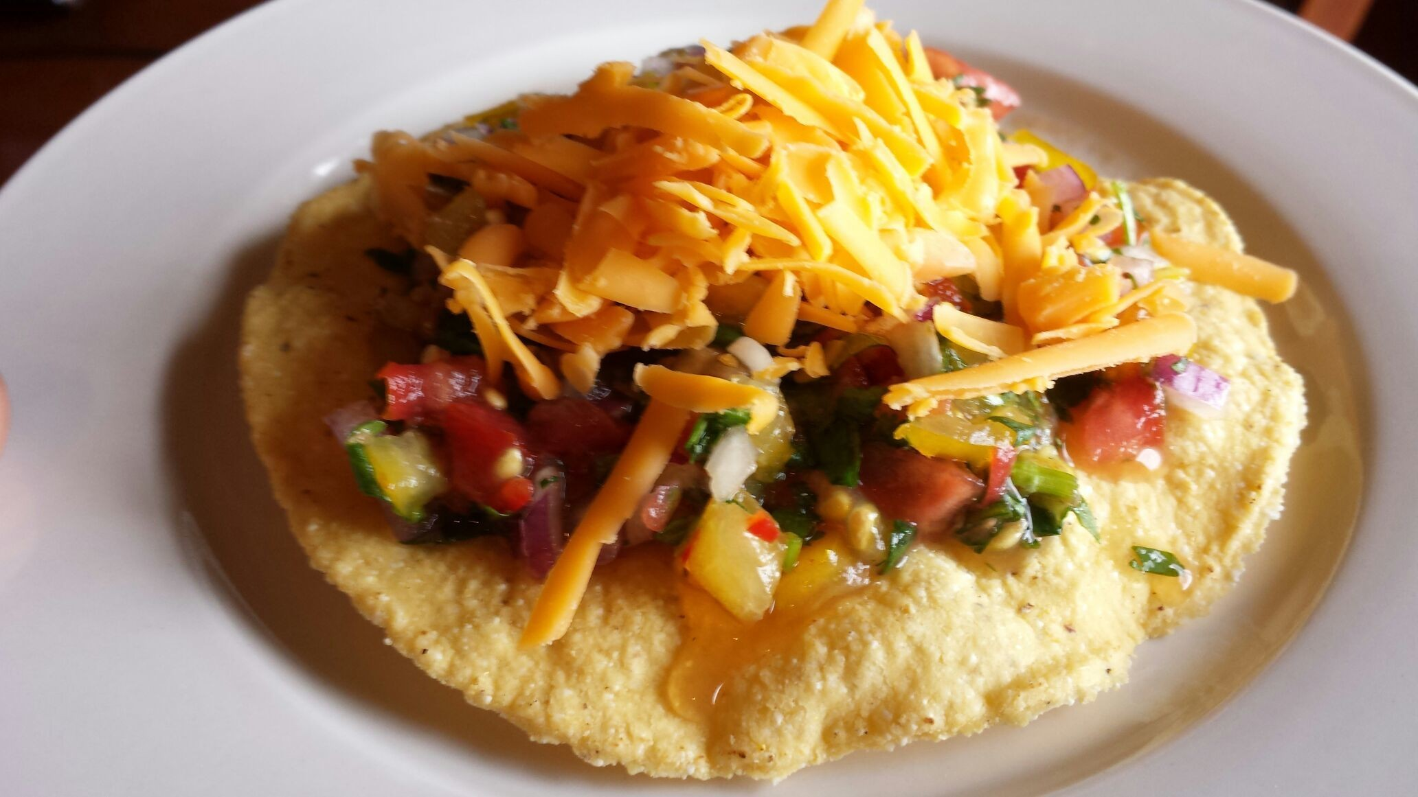 Tostada with pico de gallo and shredded cheese. Pre-dinner snack!