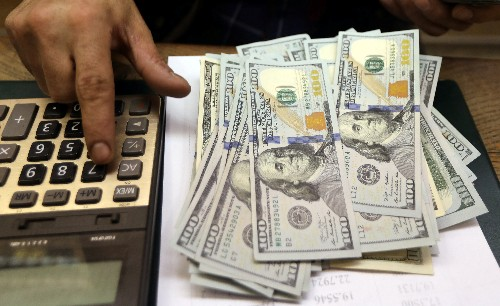 Dollar holds firm as oil jitters ease, Fed rate decision awaited