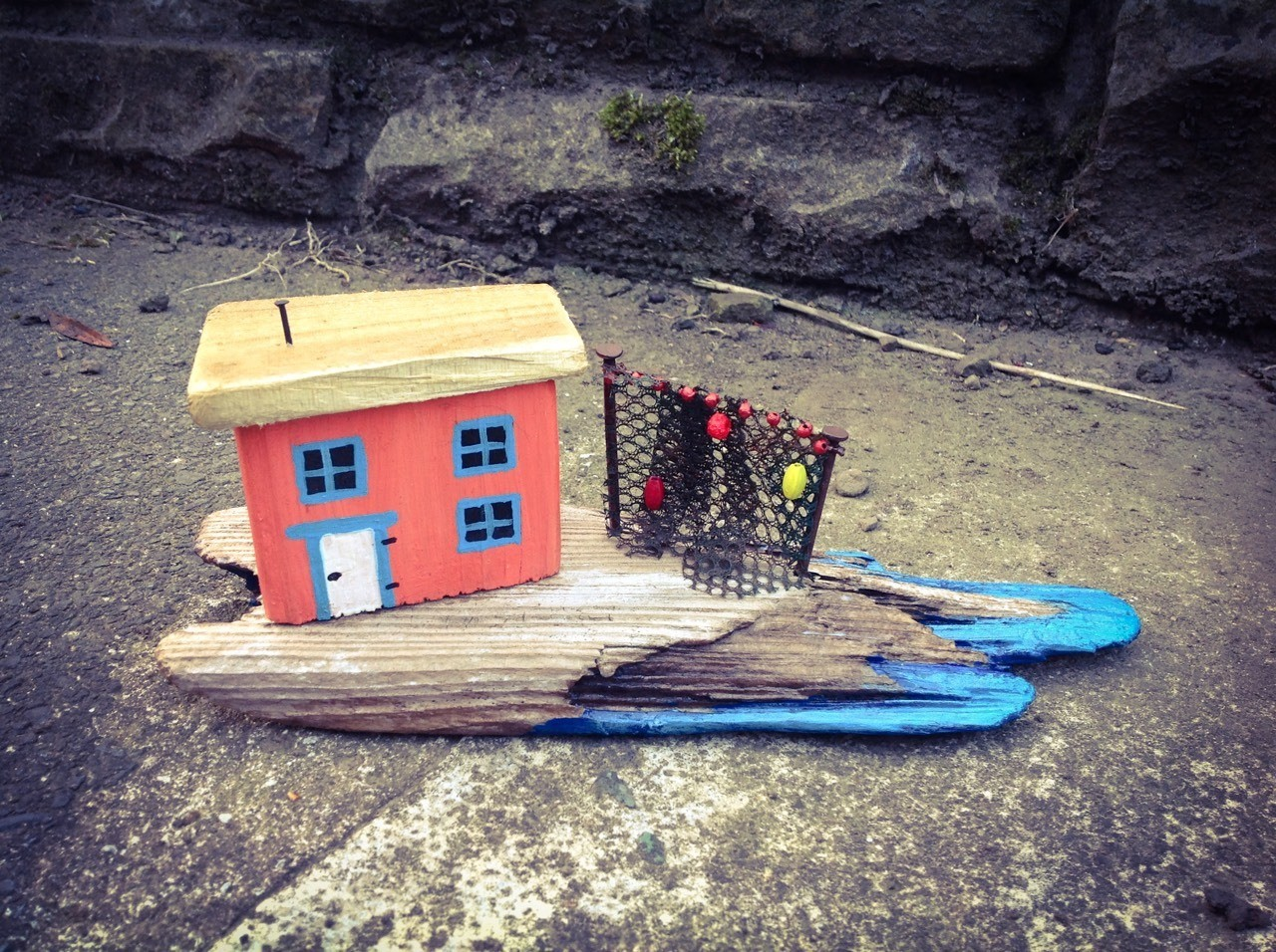 'Drying the Fishing Nets'. A peaceful little shack on its driftwood promontory by the shore of a glittering sea.
