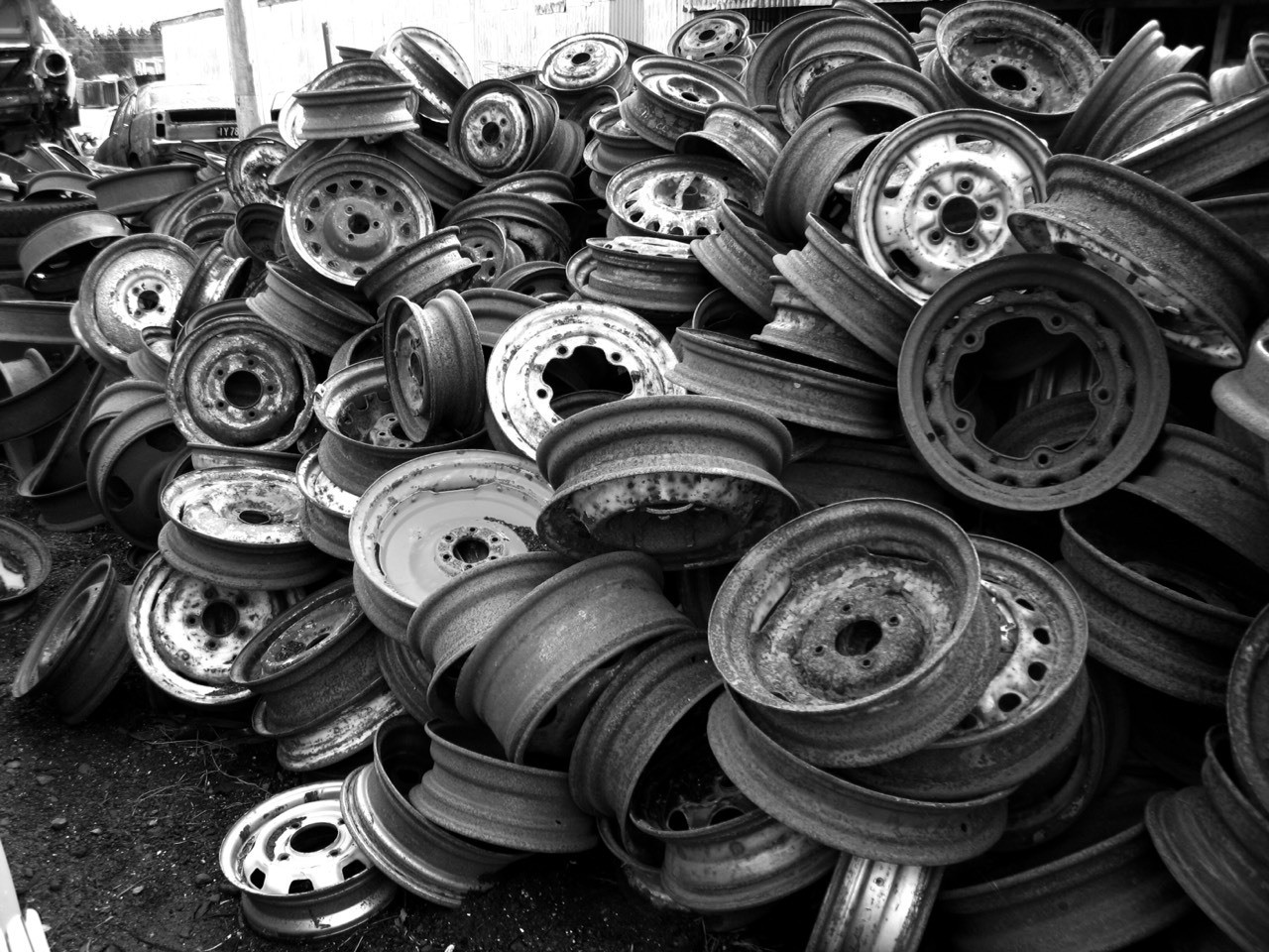 Tireless - rims sit heaped up in a pile waiting to be found, Smash Palace at Horopito north of Ohakune is a giant vehicle junkyard and a boon for those putting older cars back together. Originally a colour image redone to B&W