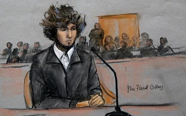 Boston bomber suspect smirks in rare court appearance