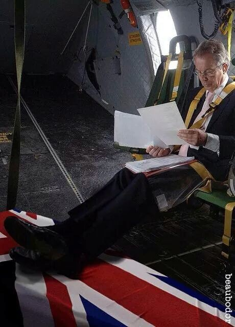 Tony Blair using a dead soldiers coffin as a foot rest