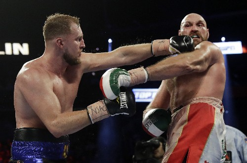 Fury overcomes bloody cut over eye to beat Wallin