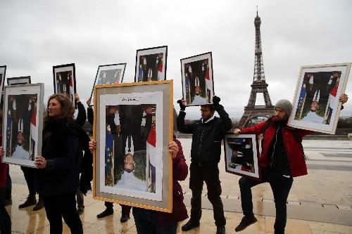 French activists use Macron portraits to urge climate action