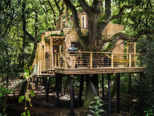 This luxury treehouse with spa deck and slide is everything