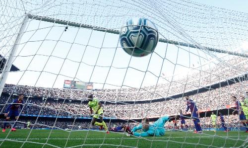 Barca sneak past Getafe to keep pressure on Real