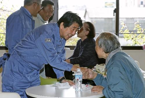Japan PM visits storm-hit areas, royal parade may be delayed
