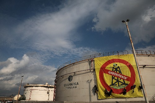 Greenpeace activists abseil down Hellenic Petroleum storage tank to protest 'climate emergency'