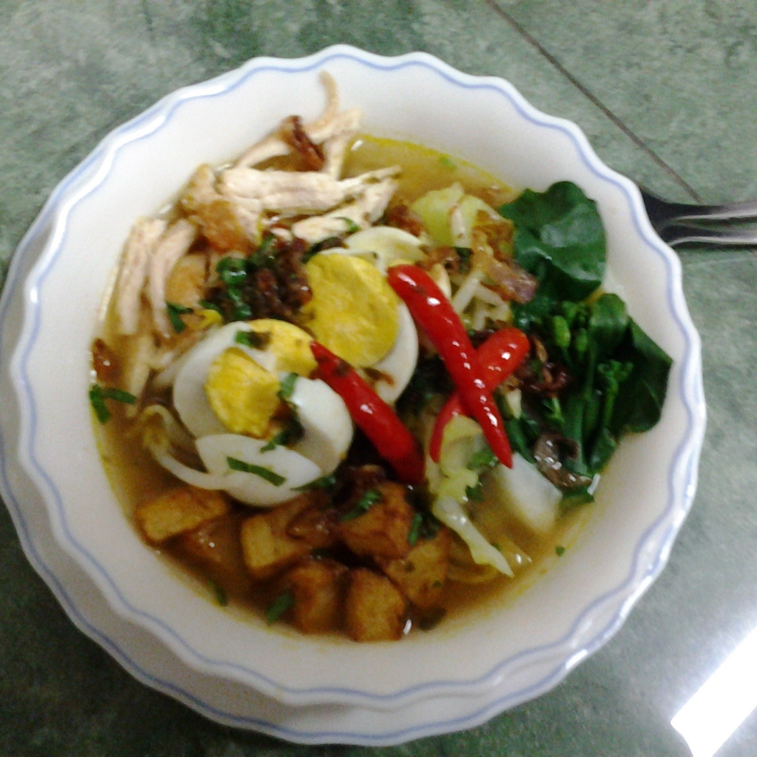 Indonesian food known as soto,yellow soup glass noodles with shredded chicken, boil egg, fried potato and veggies.