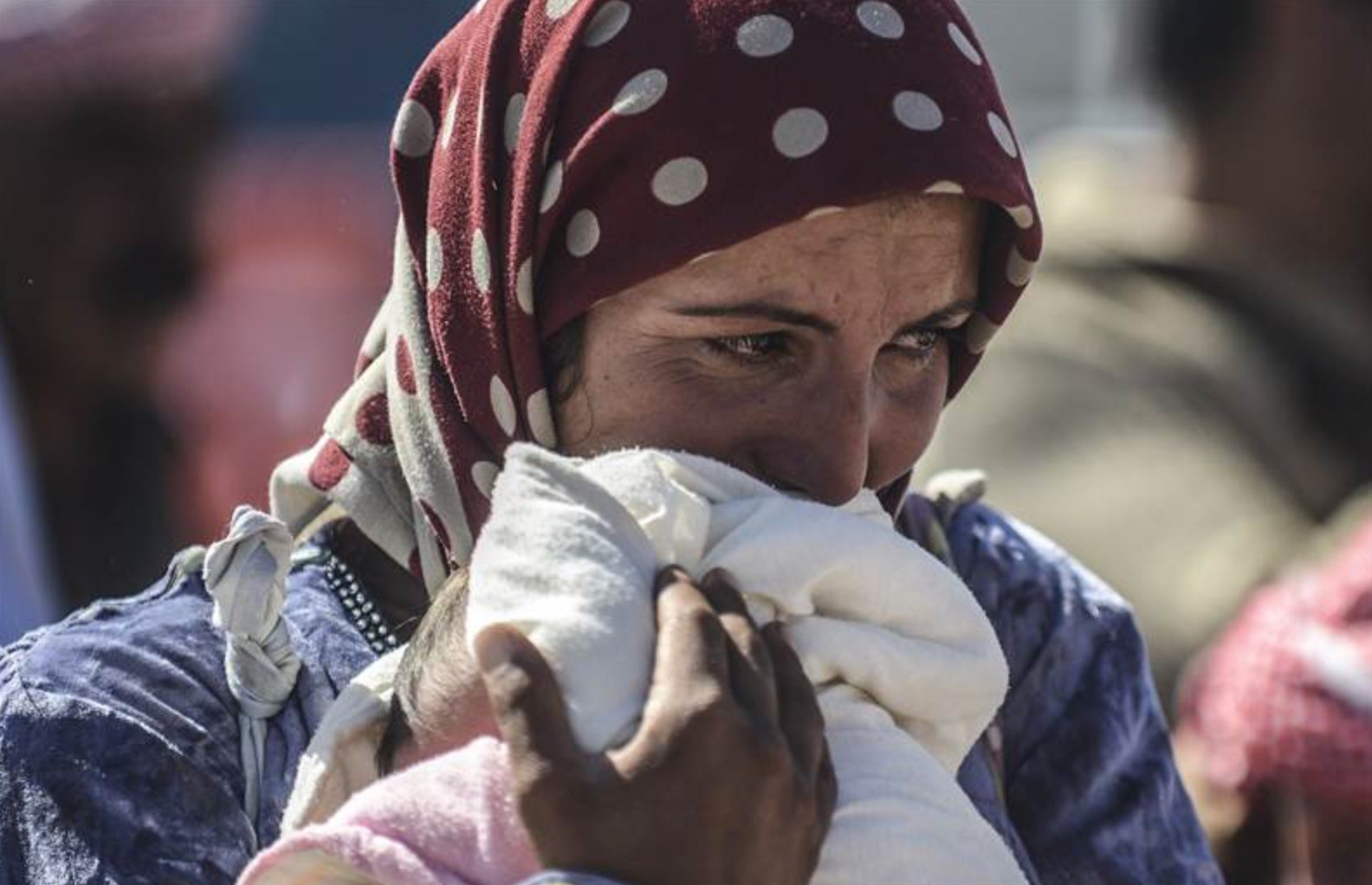 Syrian Kurdish woman cries as she holds her baby.