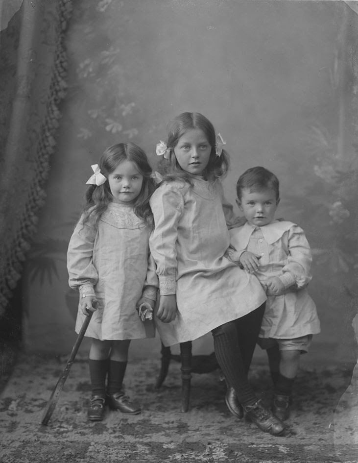"""The Murdoch Children, County Tipperary, Ireland. The photo was taken on Wednesday, September 27, 1905"" The Murdoch family has had it's roots for centuries across Ireland, England and Scotland. I was planning on digging into their genealogy, but decided it would have been a massive project. The girl on the left is Adeline Murdoch age 4-ish, the oldest sister in the middle is Caroline Murdoch - quite adorable, and the boy on the right is Sidney Murdoch age 3-ish. • Abbie Stewart • More information at National Library of Ireland on the Commons"