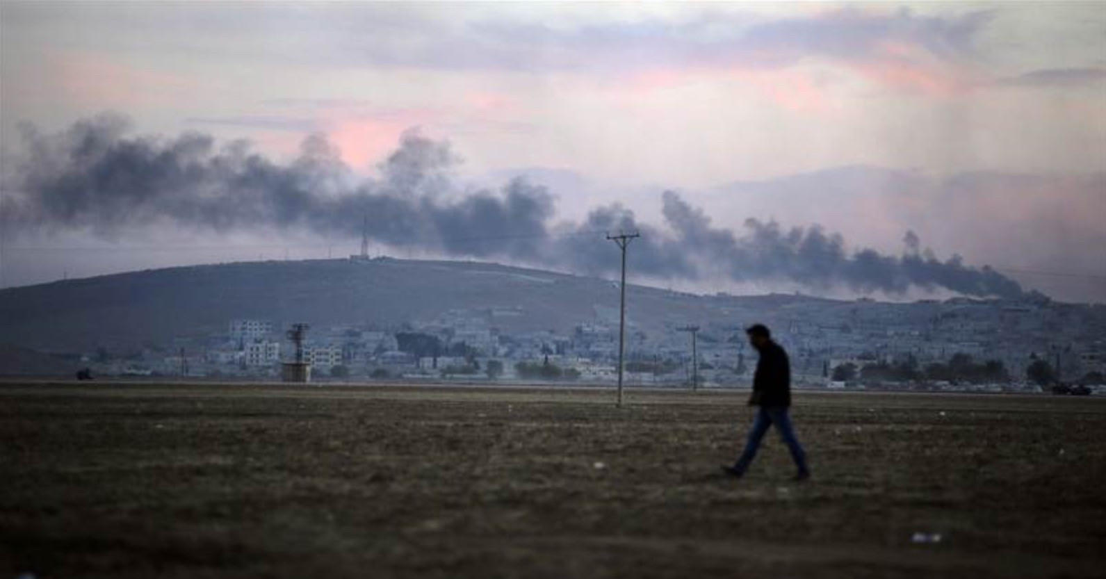 A Turkish Kurd walks in Mursitpinar on the outskirts of Suruc, at the Turkey-Syria border, as smoke from a fire caused by a strike rises over Kobani, inside Syria, on Oct. 8. Kobani and its surrounding areas have been under attack since mid-September, as fighting intensified between Syrian Kurds and Islamic State militants, with ISIS capturing dozens of nearby Kurdish villages.