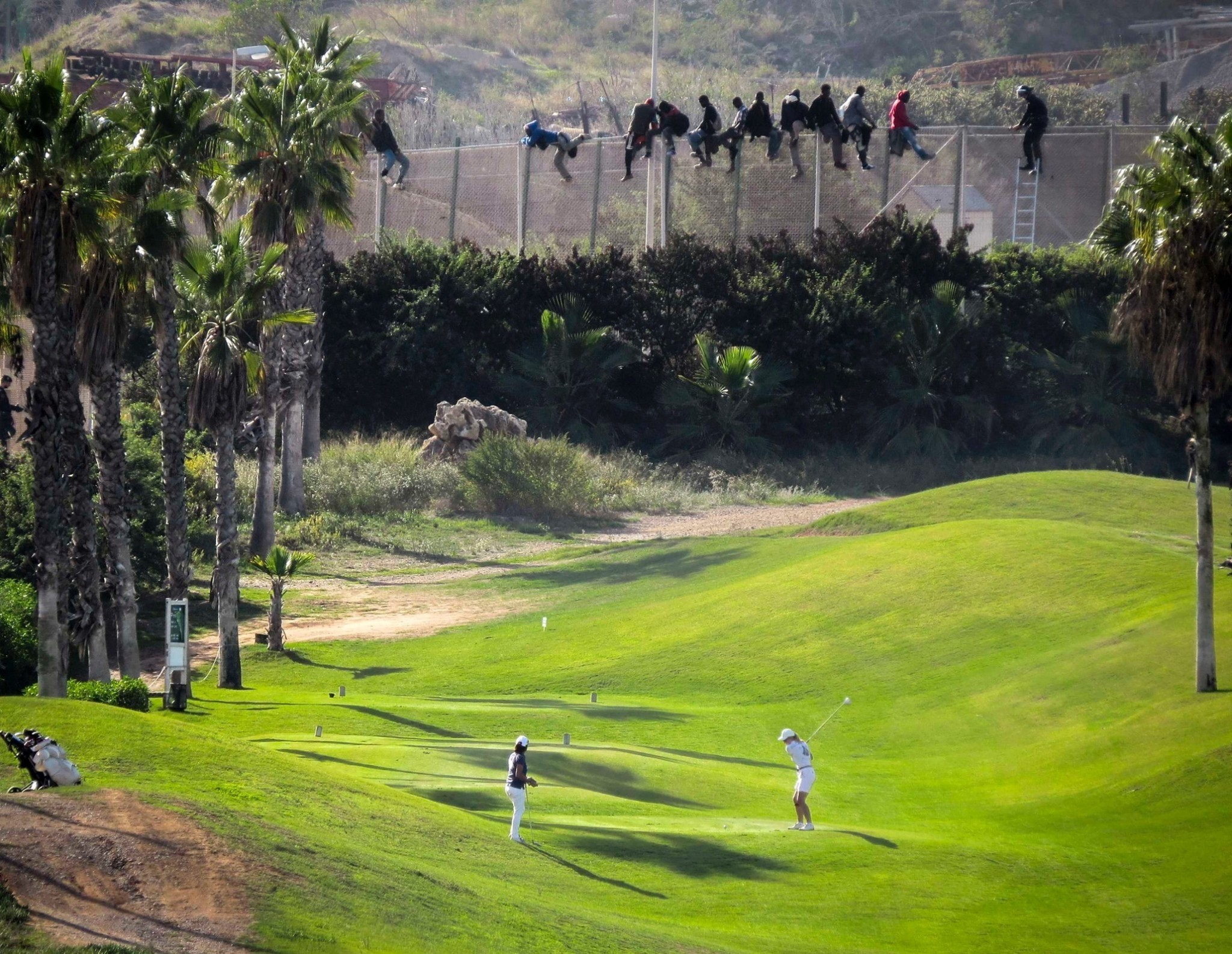 African migrants look down on white-clad golfers in viral photo
