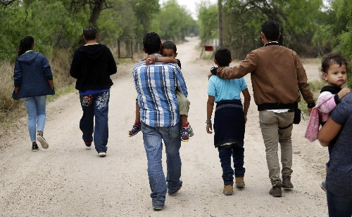 Cradling children, migrant families cross border in waves