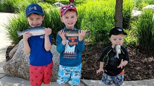 Mom doesn't realize kid shoved a rubber fish in his mouth in family photo
