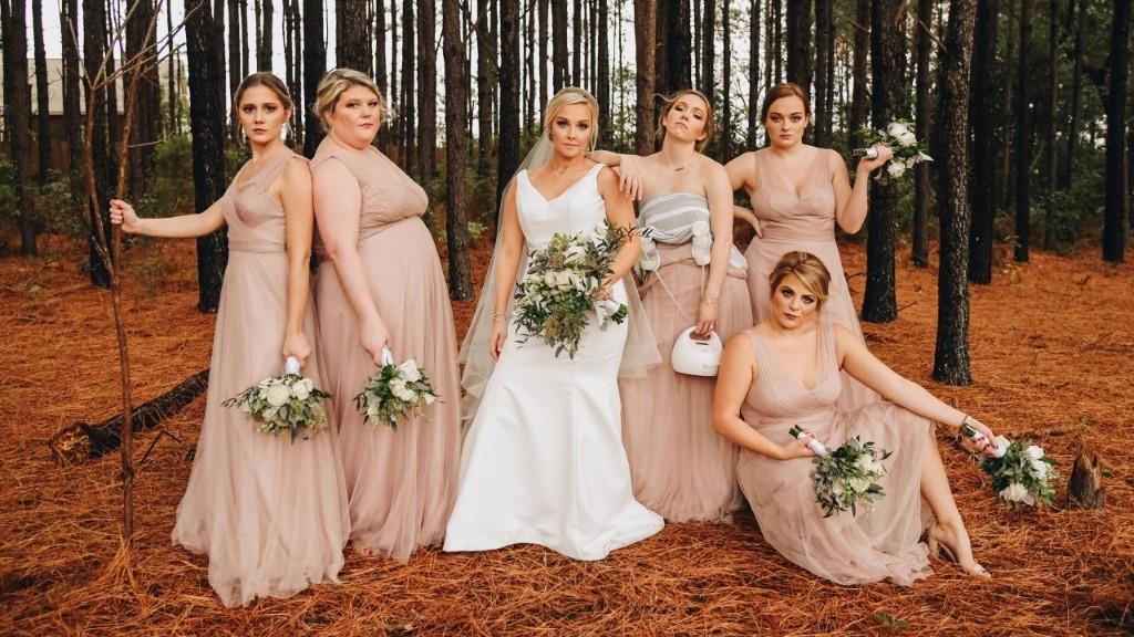 Breastfeeding bridesmaid posed while pumping milk during wedding photoshoot