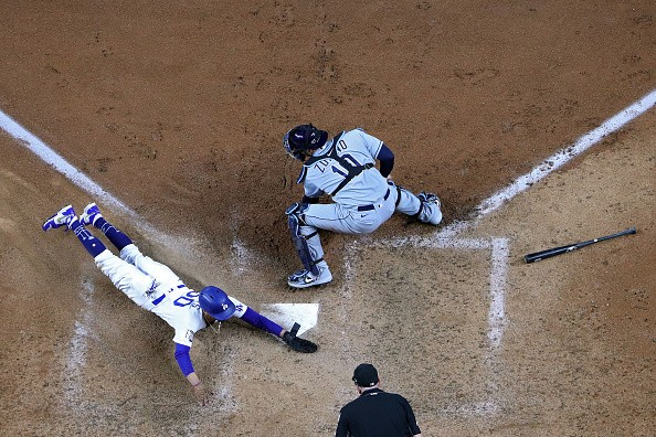 Mookie Betts of the Los Angeles Dodgers slides in safely past Mike...