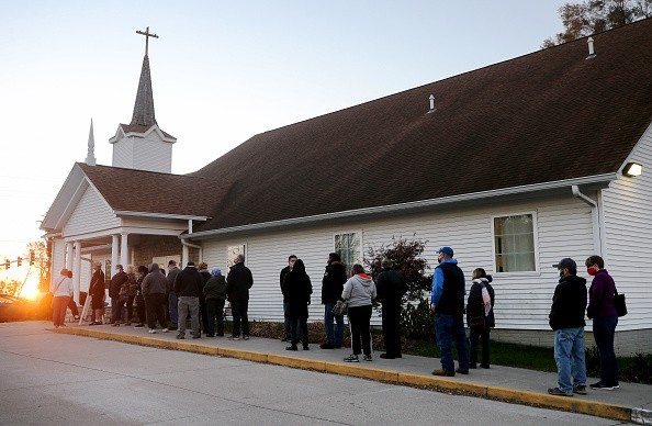 Des Moines, Iowa where people stand in line to vote as the sun rises