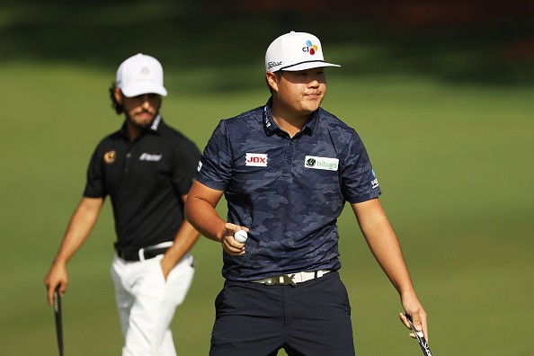 Sungjae Im of Korea reacts after making a putt on the second green...
